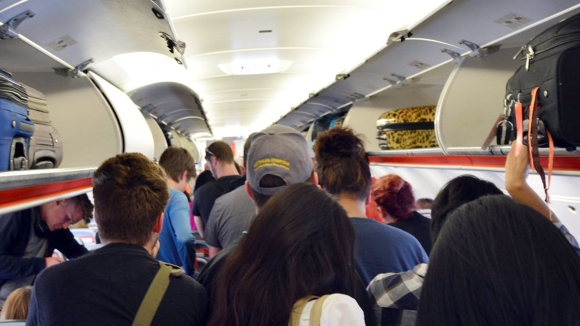 people standing to get out of airplane