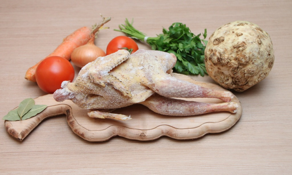 Frozen chicken on a cutting board with vegetables