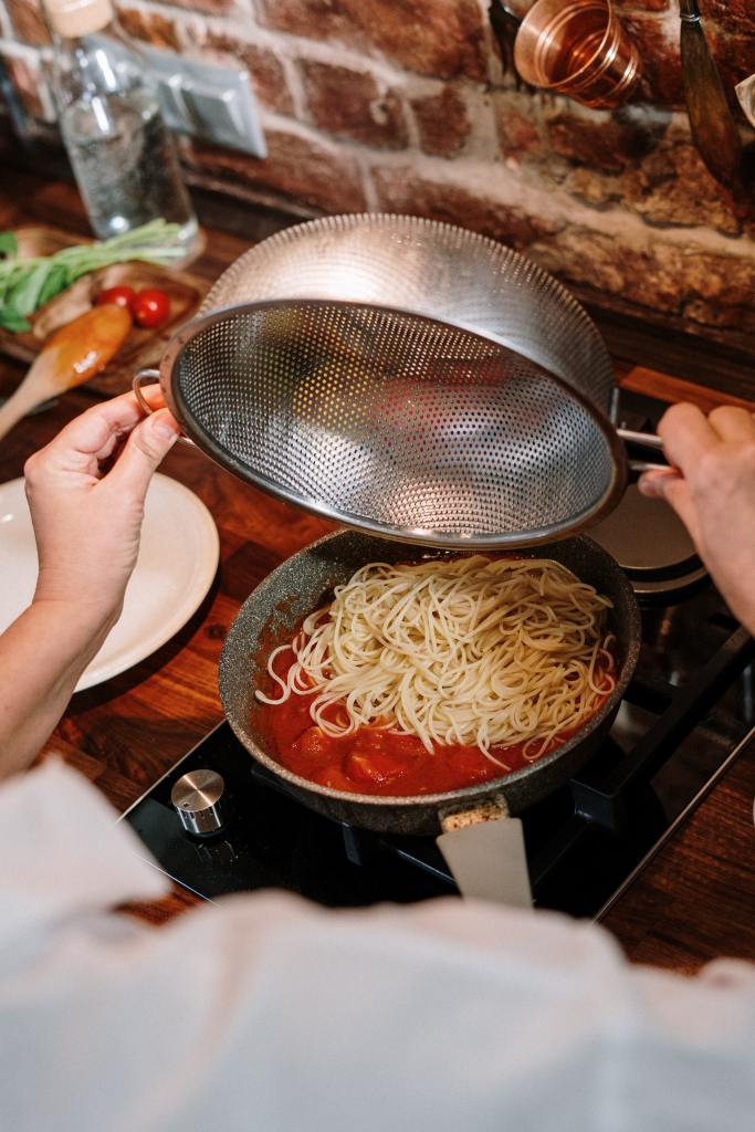Person pouring pasta from a colander into a pan of sauce